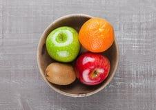 Äpplen med kiwin och apelsinen i träbunke Royaltyfri Fotografi