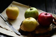 Äpplen med kniven och kanelbruna vattendroppar på trätabellen för hantverkpapperssvart, tillbaka ljus Royaltyfria Bilder