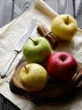 Äpplen med kniven och kanelbruna vattendroppar på trätabellen för hantverkpapperssvart, tillbaka ljus Arkivbilder