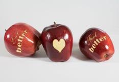 3 äpplen med orden - äta bättre bättre känsel - och en hjärta Arkivbild
