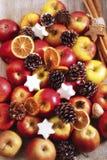 Äpplen, muttrar, julkakor och kanelbruna pinnar Arkivbild