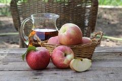 Äpplen Nya äpplen i en vide- korg på en trätabell Royaltyfri Bild