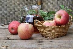 Äpplen och äppelmust Nya äpplen i en vide- korg och en Appl Royaltyfri Fotografi