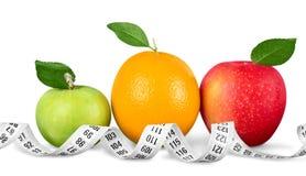 Äpplen och apelsin med att mäta bandet som isoleras på Royaltyfria Foton