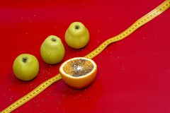 Äpplen och apelsin som mäta tejpar på en röd bakgrund royaltyfria bilder