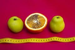 Äpplen och apelsin som mäta tejpar på en rosa bakgrund Arkivfoto