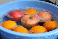 Äpplen och apelsiner i vatten Arkivfoton