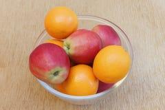 Äpplen och apelsiner på exponeringsglas pläterar. Royaltyfri Bild