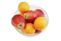 Äpplen och apelsiner på exponeringsglas pläterar, isolerat. Arkivbilder