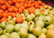 Äpplen och apelsiner på marknaden Arkivfoto