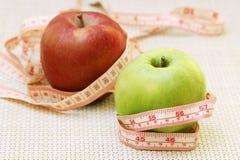 Äpplen och böjlig linjal som ett begrepp av banta och viktkontroll royaltyfri fotografi