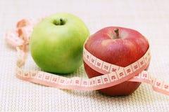 Äpplen och böjlig linjal som ett begrepp av banta och viktkontroll royaltyfria bilder