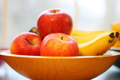 Äpplen och bananer i en träbunke Fotografering för Bildbyråer