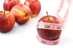 Äpplen och band som mäter på vit bakgrund Arkivfoton