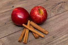 Äpplen och kanelbruna pinnar överst av en tabell Royaltyfri Fotografi