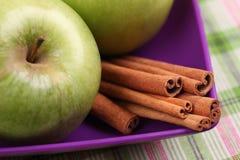 Äpplen och kanelbruna pinnar i en bunke Arkivbilder