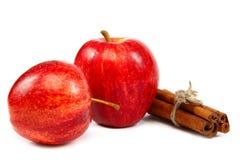 Äpplen och kanelsticks på vit bakgrund Arkivbild