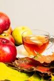 Äpplen och lönnlöv på tabellen bredvid en kopp te Fotografering för Bildbyråer