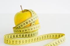Äpplen och mätabandet som föreslår, bantar begrepp Arkivfoto