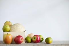 Äpplen och melon med en vit bakgrund Royaltyfria Bilder