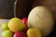 Äpplen och melon på trä Arkivfoto