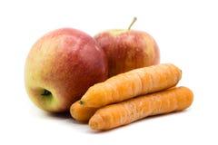 Äpplen och morötter som isoleras på vit bakgrund arkivbilder