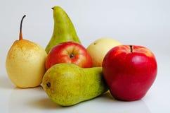 Äpplen och päron på en grå bakgrund Arkivbilder
