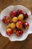 Äpplen och vit bunke för citroner Arkivbild