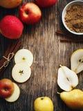 Äpplen, päron, kanelbruna pinnar och farin på träbackgro Arkivfoto