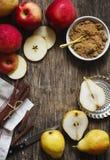 Äpplen, päron, kanelbruna pinnar och farin på träbackgro Arkivbild