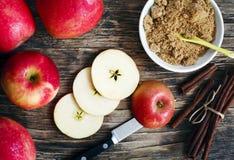 Äpplen, päron, kanelbruna pinnar och farin på träbakgrund Arkivfoto