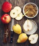 Äpplen, päron, kanelbruna pinnar och farin på träbakgrund Royaltyfri Bild
