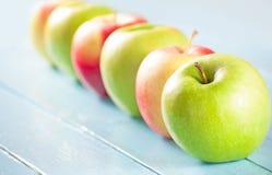 Äpplen på blå wood bakgrund Royaltyfri Fotografi