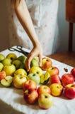Äpplen på den vita tabellen Söta äpplen på tabellen på ljus backgrou Fotografering för Bildbyråer