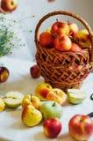 Äpplen på den vita tabellen Söta äpplen på tabellen på ljus backgrou Arkivfoton