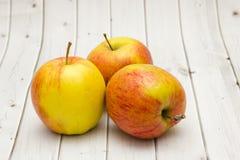 Äpplen på en träbakgrund Arkivbild