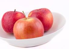 Äpplen på en vit platta Arkivbild