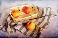 Äpplen på kökshandduken och i korg Royaltyfria Bilder