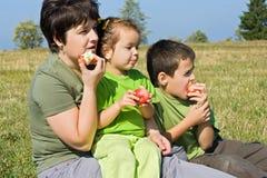 äpplen som äter den lyckliga familjen Royaltyfria Bilder