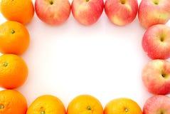 äpplen som bildar ramfruktapelsiner Arkivfoton