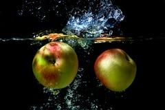 äpplen som faller för att water Arkivbilder