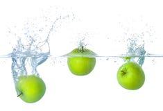 Äpplen som faller in i vatten med färgstänk Arkivfoton