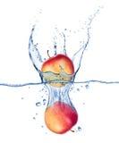Äpplen som faller under vatten med en färgstänk på vit Arkivfoto