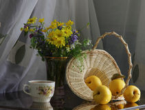 Äpplen, wattled korg och vårbukett Arkivfoto