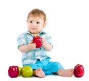 äpplet behandla som ett barn den härliga pojken äter red Royaltyfri Fotografi