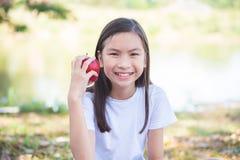 Äpplet och leenden för flicka parkerar det hållande in Arkivbild