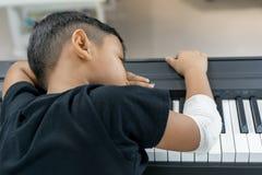 Är asiatiska pojkar på de sårade händerna sömn på pianot Arkivbild