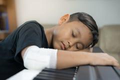 Är asiatiska pojkar på de sårade händerna sömn på pianot Fotografering för Bildbyråer