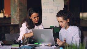 Är attraktiva kvinnor för kvinnliga coworkers tala och genom att använda bärbar datorsammanträde på skrivbordet i delat kontor mo arkivfilmer