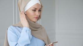 Är bärande hijab för den muslimska kvinnan lyssnande musik i smartphone genom att använda den trådlösa hörluren arkivfilmer
